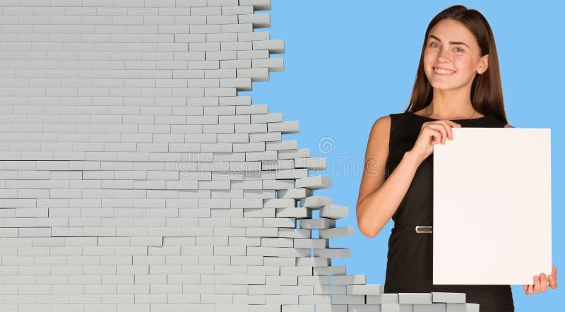 拿着白纸板料的美丽的女实业家 免版税库存照片
