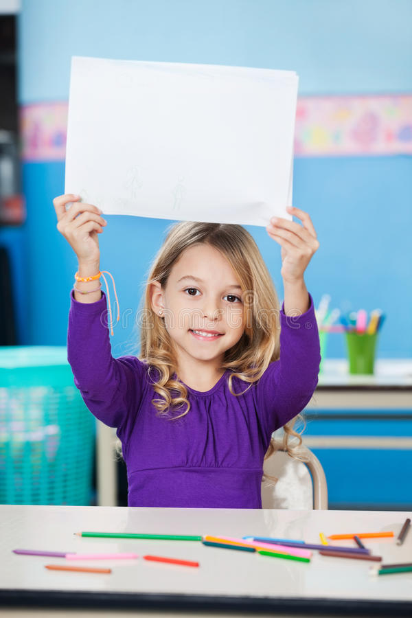 拿着白纸的女孩在书桌在教室 库存照片