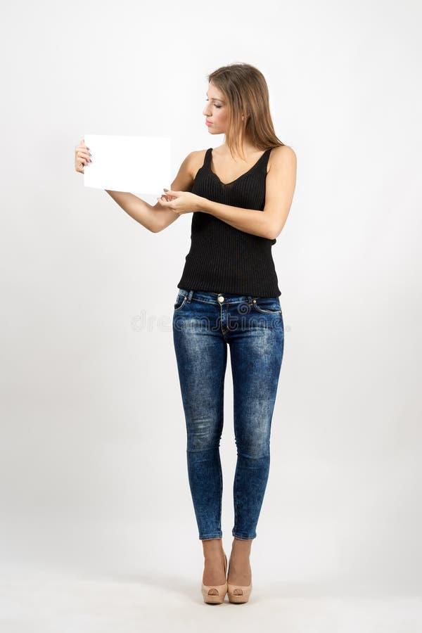 拿着白纸的年轻美丽的妇女 免版税库存照片