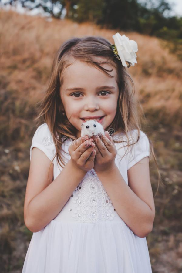 拿着白色仓鼠-减速火箭的神色的好微笑的女孩 免版税库存图片