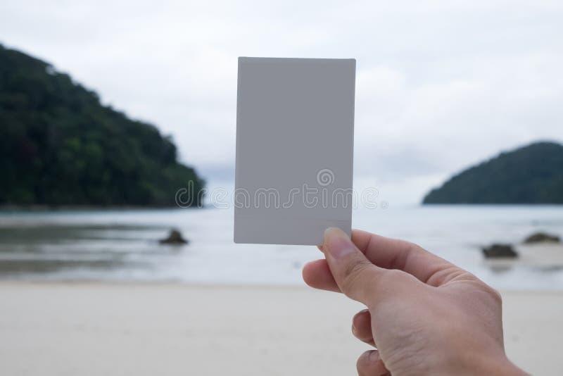 拿着白色偏正片影片的妇女的手站立在海滩与 免版税库存照片
