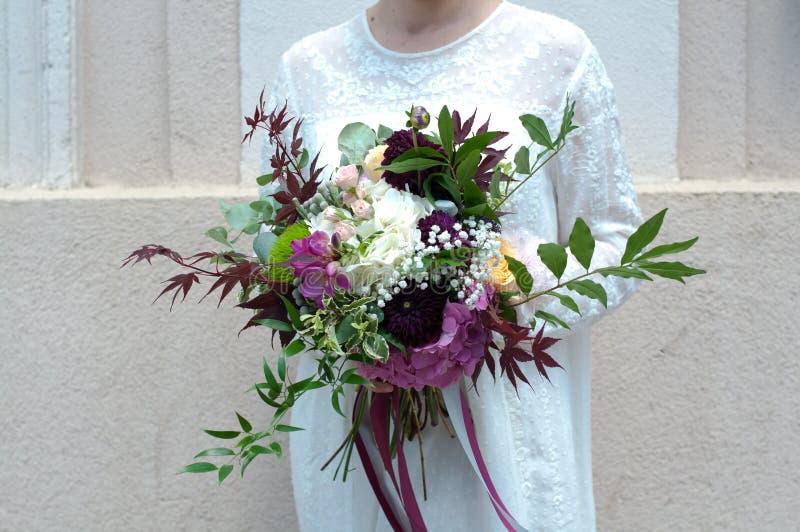 拿着白色八仙花属、牡丹和玫瑰的五颜六色的婚姻的花花束新娘 免版税库存照片