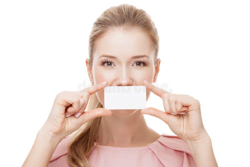 拿着白色卡片的美丽的妇女在前边她的嘴唇  查出 库存图片