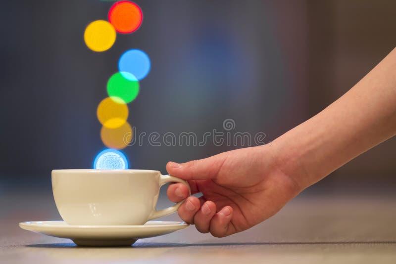 拿着白色咖啡与五颜六色的bokeh蒸汽的人的手 免版税库存照片