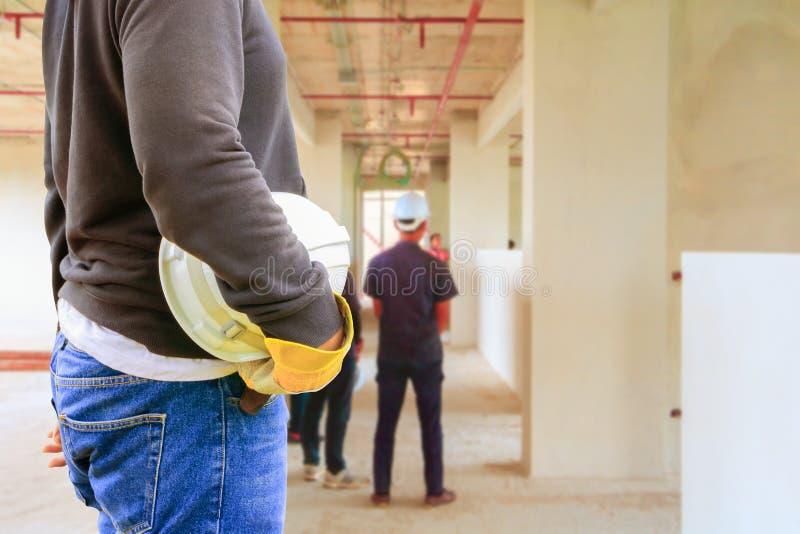 拿着白色安全帽子内部的工程学手更新房子运作的建造场所 库存图片