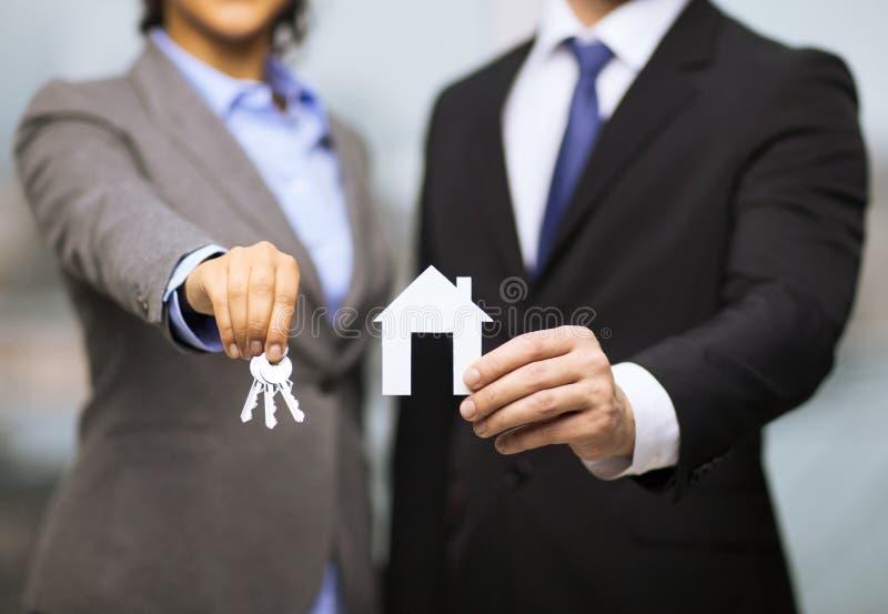 拿着白色房子的商人和女实业家 免版税库存照片