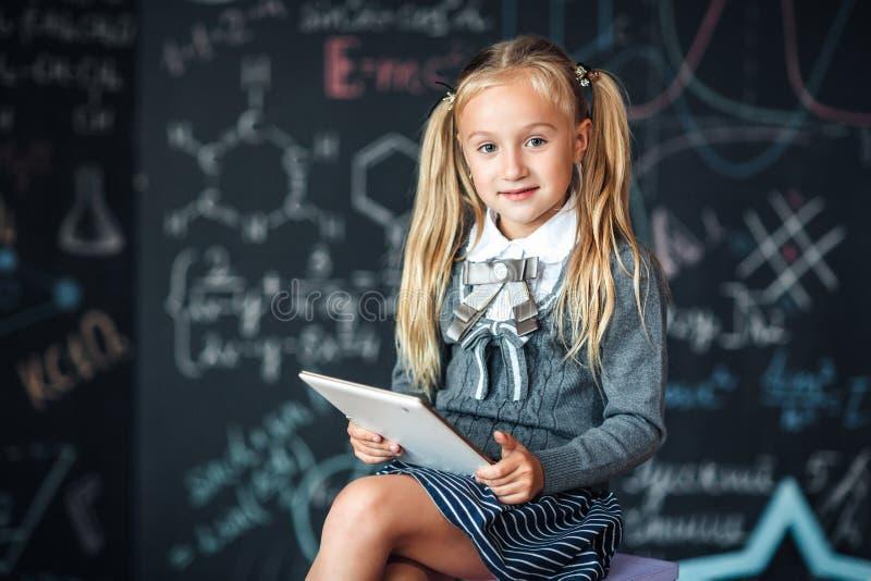 拿着白色数字片剂的校服的可爱的矮小的白肤金发的女小学生 黑板有学校惯例背景 backarrow 免版税图库摄影