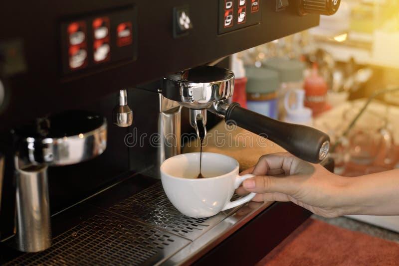 拿着白色杯子用热的咖啡的妇女手 免版税库存照片