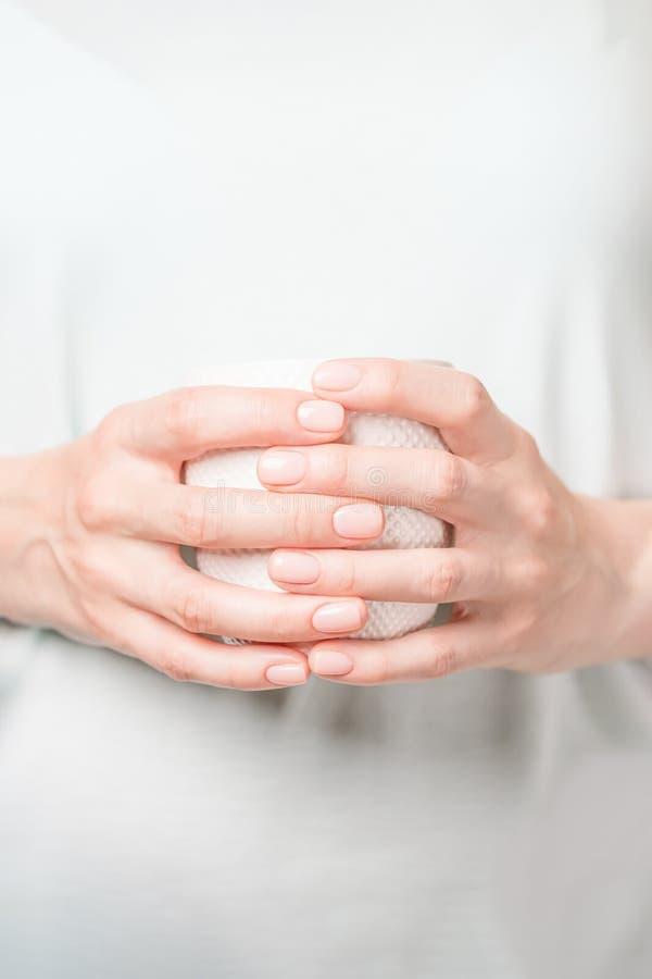 拿着白色杯子的美好的女性手 与裸体指甲油的修指甲 r 免版税图库摄影