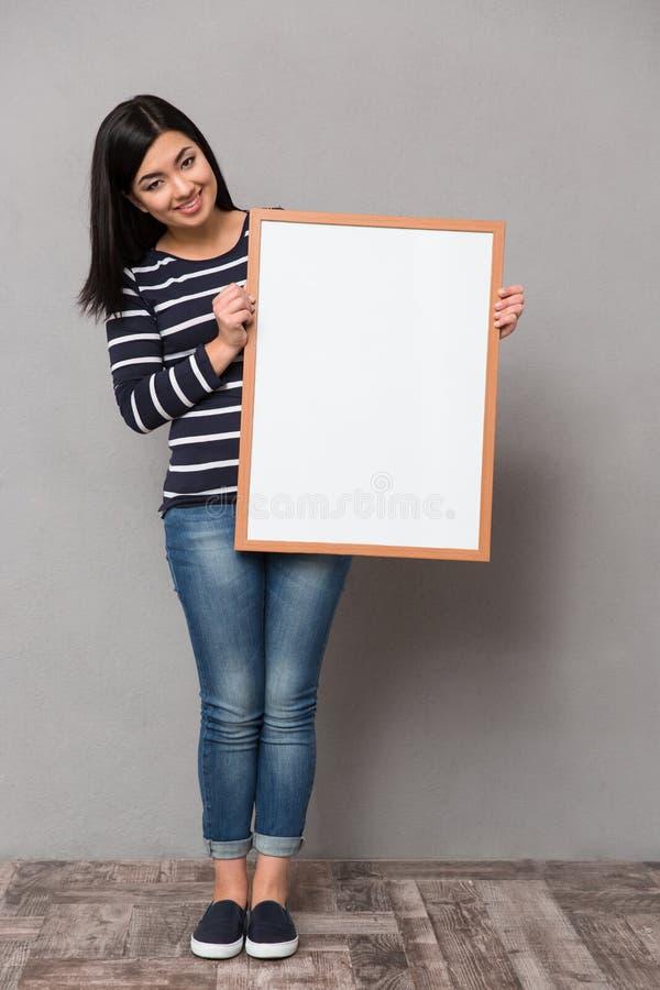 拿着白色框架的亚裔女孩 库存图片