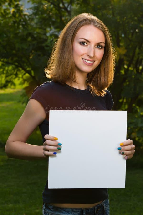拿着白色白纸的愉快的微笑的女孩 库存照片
