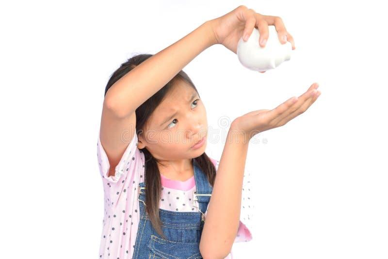 拿着白色的小亚裔女孩画象存钱罐 图库摄影