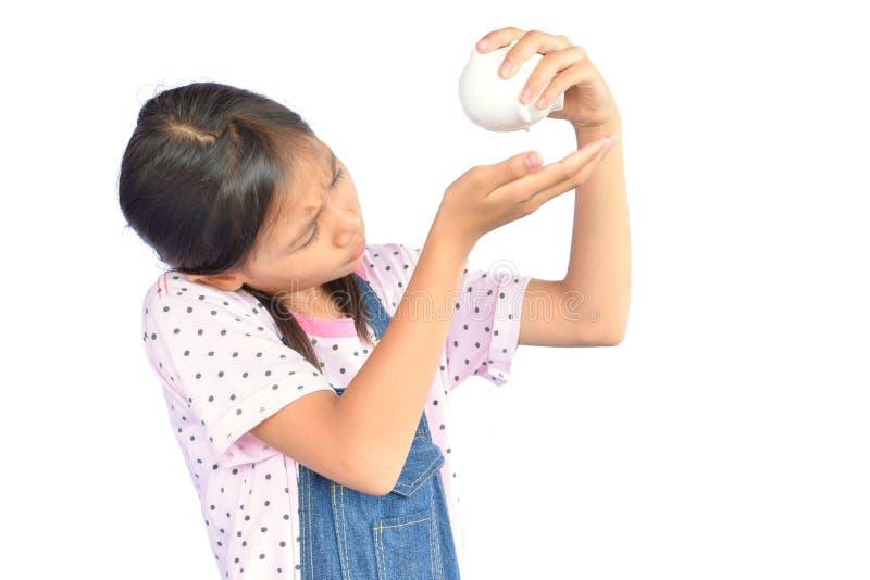 拿着白色的小亚裔女孩画象存钱罐 库存图片