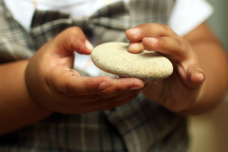 拿着白色石头的婴孩手指 1岁婴孩的手 免版税库存照片