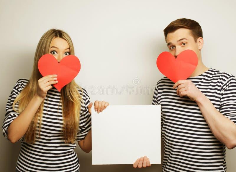拿着白色空白和红色心脏的愉快的夫妇 免版税库存图片