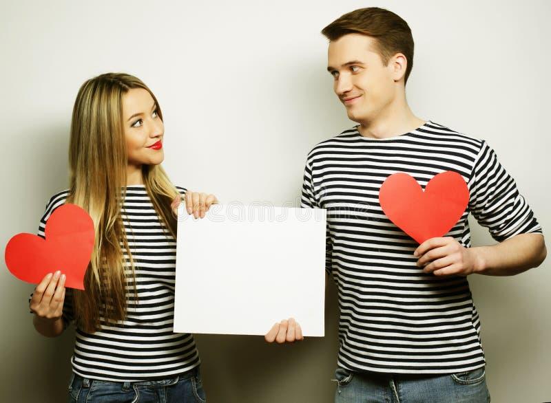 拿着白色空白和红色心脏的愉快的夫妇 库存照片