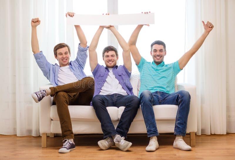拿着白色空白的横幅的微笑的男性朋友 免版税库存照片