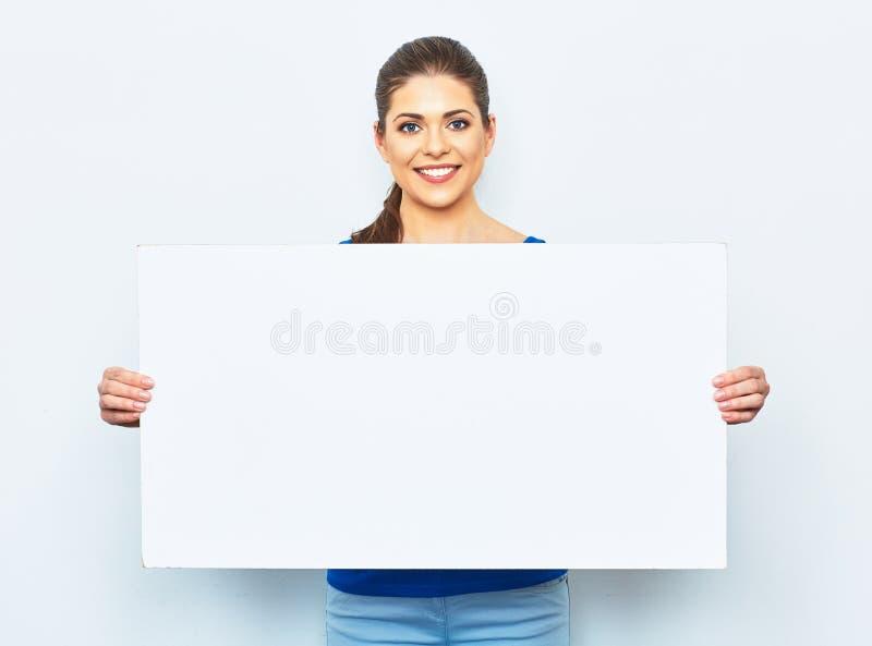 拿着白色空白的牌的少妇 库存图片