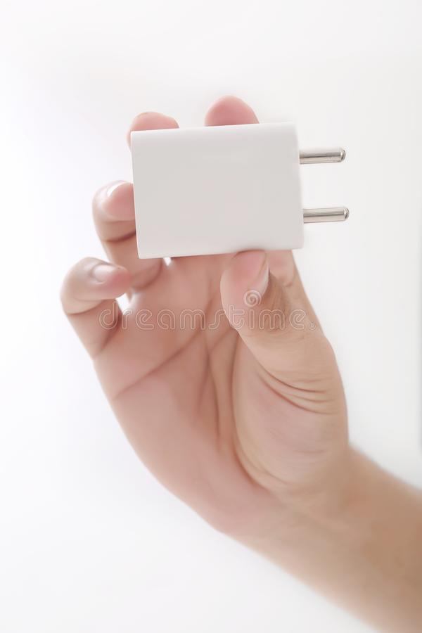 拿着白色适配器的人手中 图库摄影