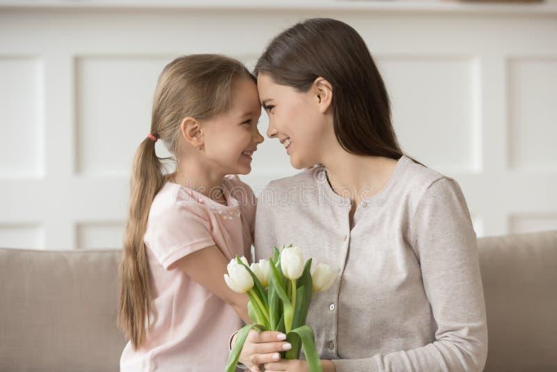拿着白色郁金香的愉快的母亲接触有女儿的前额 免版税图库摄影