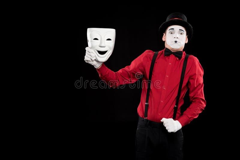 拿着白色面具的害怕的笑剧 免版税库存图片