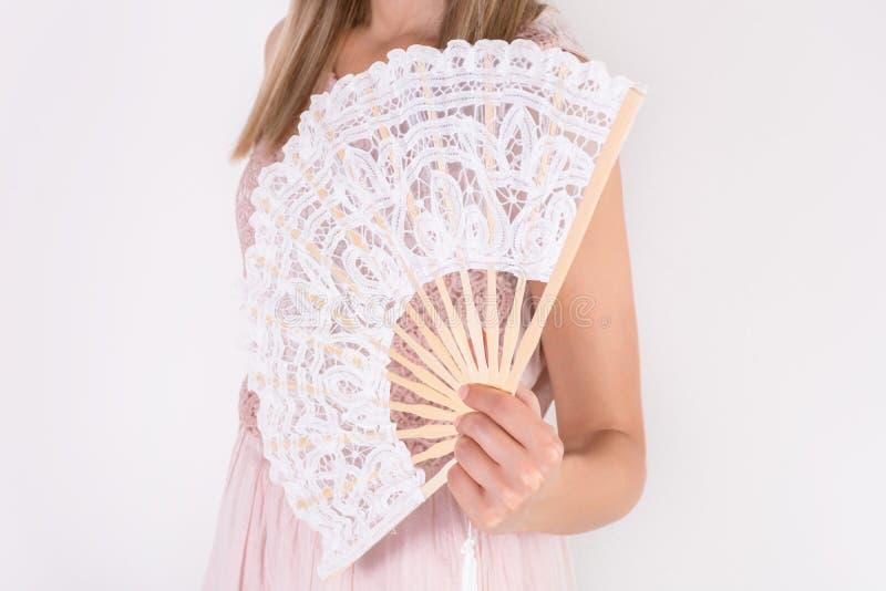 拿着白色鞋带手爱好者的奶油色礼服的女性 免版税库存照片