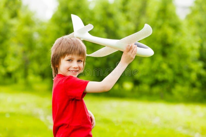 拿着白色飞机玩具的微笑的男孩单独 免版税库存图片
