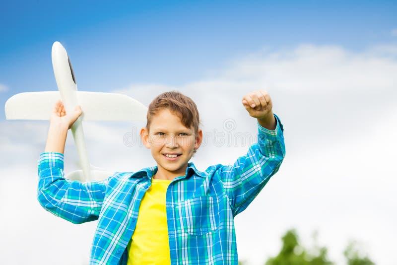 拿着白色飞机玩具的微笑的男孩画象 免版税库存图片