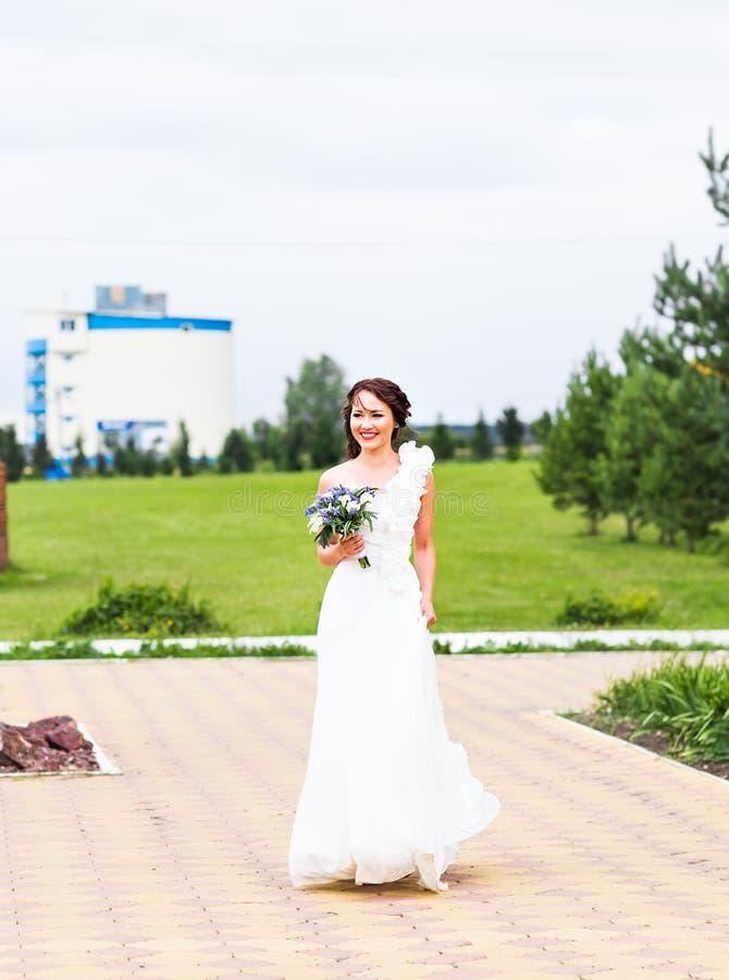 拿着白色水芋百合和蓝色花的花束新娘 库存照片