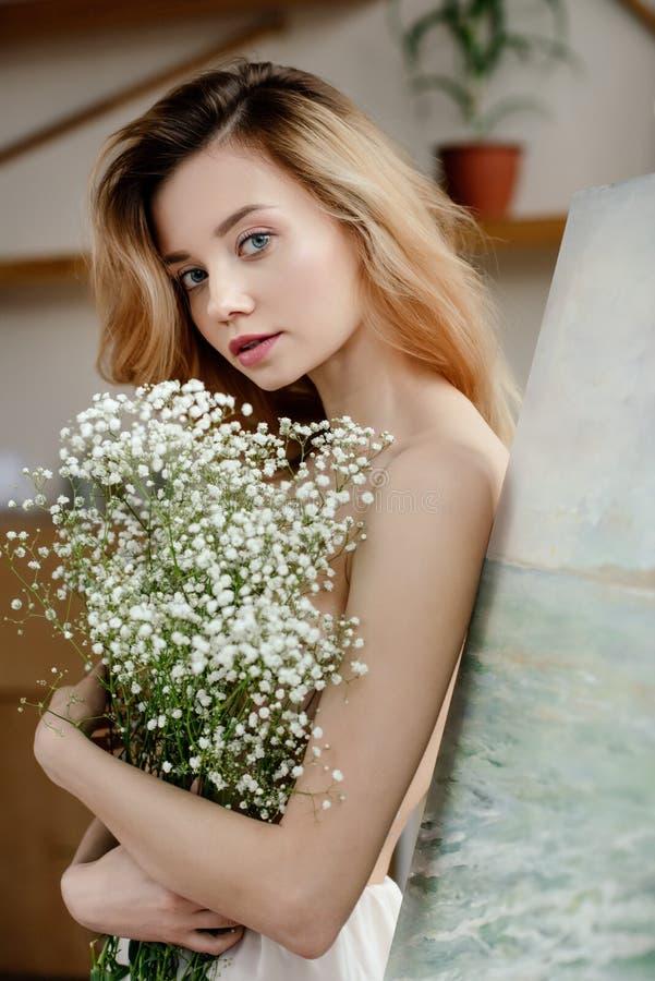 拿着白花和看照相机的美丽的嫩女孩在艺术演播室 图库摄影
