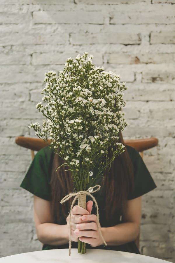 拿着白花的花束妇女 免版税库存照片