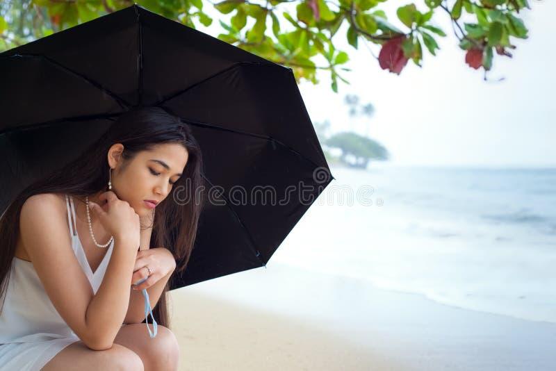 拿着的伞哀伤的青少年的女孩在多雨夏威夷海滩 库存照片