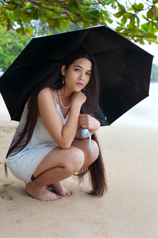 拿着的伞哀伤的青少年的女孩在多雨夏威夷海滩 库存图片