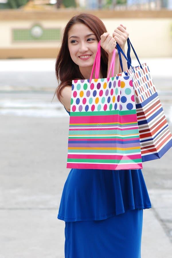 拿着的很多购物袋亚裔妇女在超级市场上 图库摄影