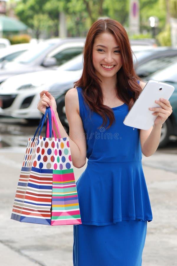 拿着的很多购物袋亚裔妇女在超级市场上 免版税图库摄影