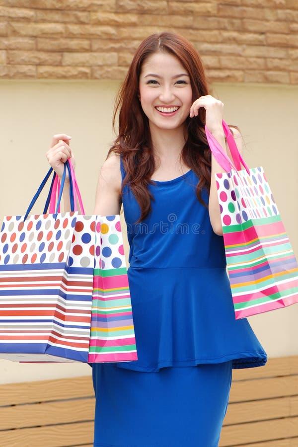 拿着的很多购物袋亚裔妇女在超级市场上 库存照片