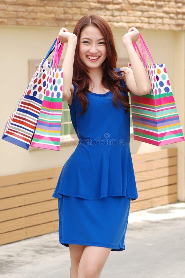 拿着的很多购物袋亚裔妇女在超级市场上 免版税库存图片