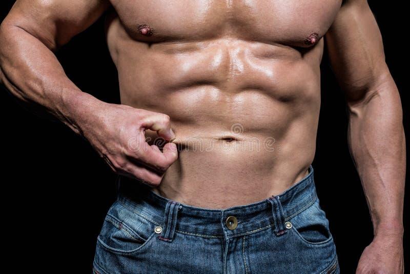 拿着皮肤的肌肉人的中央部位 库存照片