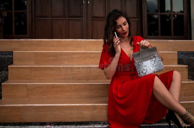 拿着皮革snakeskin Python袋子,典雅的成套装备的红色drees的时兴的女孩 在昂贵的别墅附近的模型 免版税库存图片