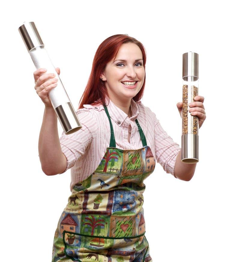 拿着盐和胡椒磨的妇女厨师 库存照片