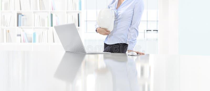 拿着盔甲工作的妇女在有计算机的书桌在办公室, PR 免版税图库摄影