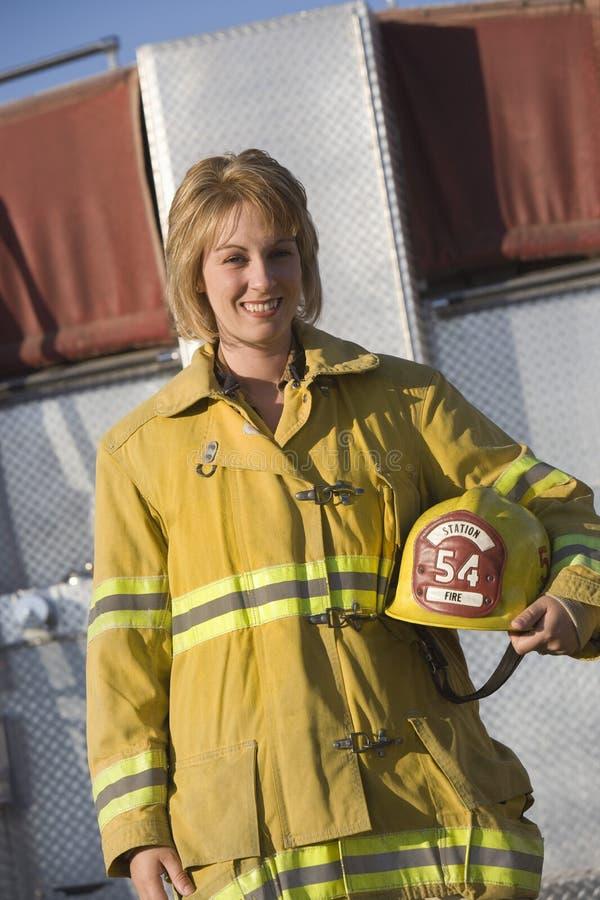 拿着盔甲的一名女性消防队员的画象 免版税库存照片