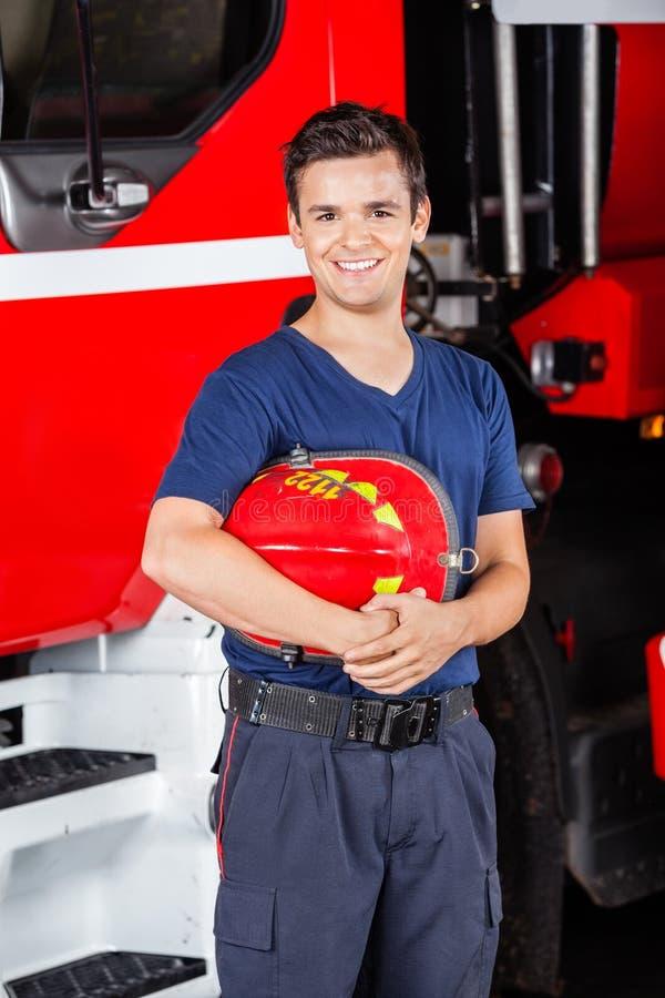 拿着盔甲的愉快的消防队员在消防局 库存照片