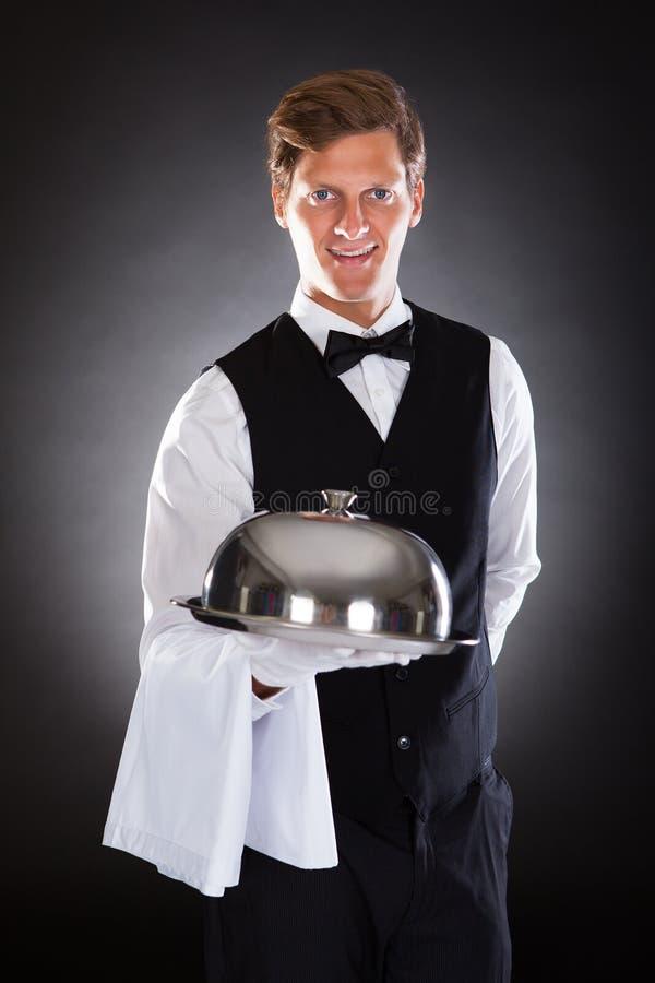拿着盘子和盒盖的男性侍者 图库摄影