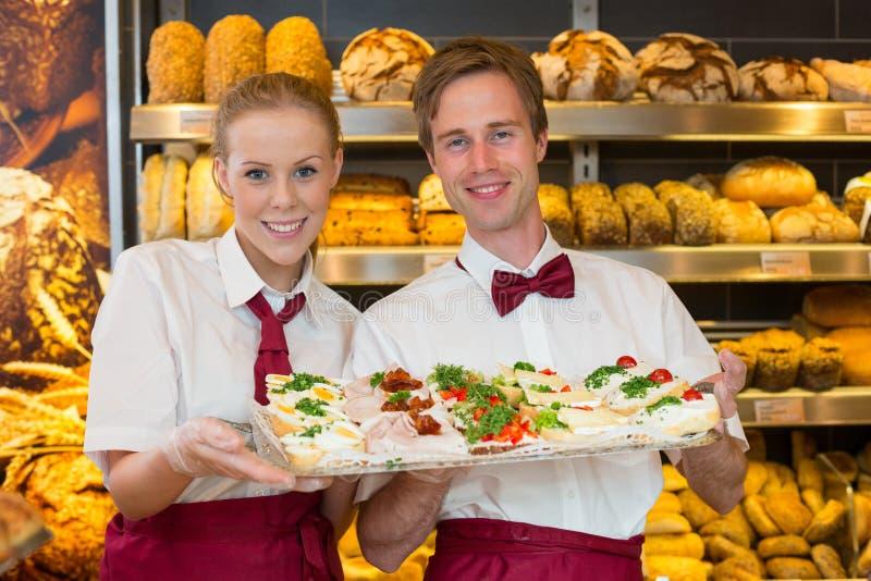 拿着盘子用三明治的两位面包师在面包店 免版税库存图片