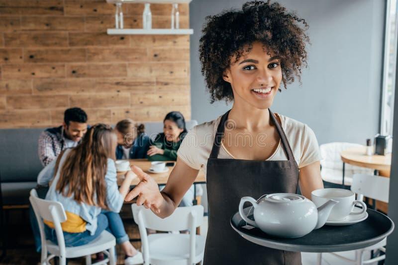 拿着盘子用茶和顾客的微笑的非裔美国人的女服务员坐在她后 免版税库存图片