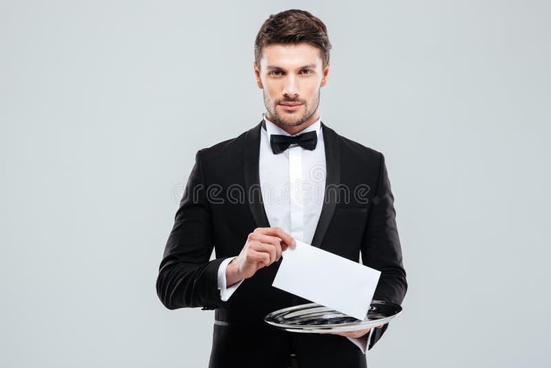 拿着盘子的无尾礼服的英俊的年轻侍者 免版税库存图片