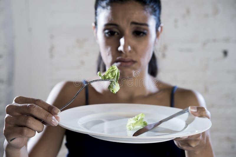 拿着盘用可笑莴苣的少妇作为她的疯狂的饮食营养混乱的食物标志 免版税库存照片