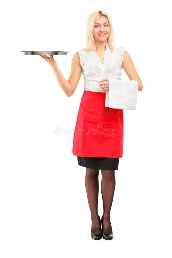拿着盘的一位微笑的女性女服务员的全长纵向 库存照片