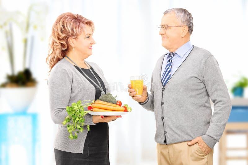 拿着盘的成熟夫妇看其中每一的有很多菜 免版税库存照片